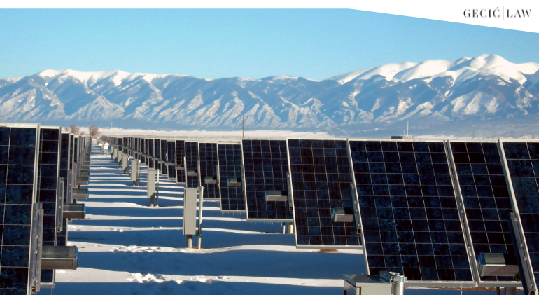 Solar panels are seen under snowy mountains as state aid and climate change become an increasingly interesting topic for investors.
